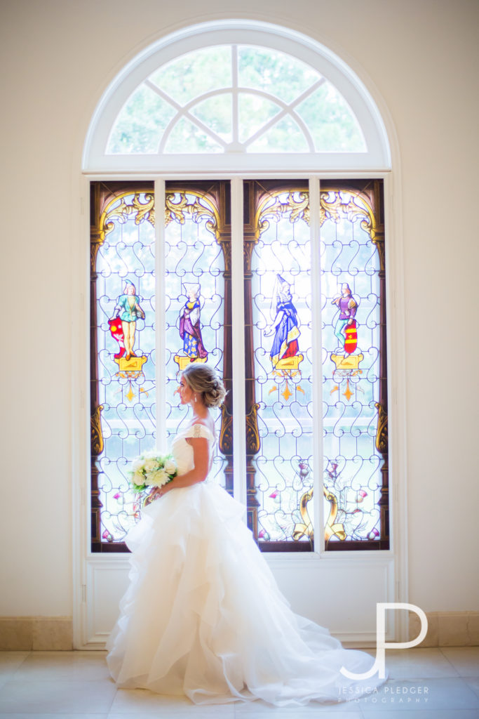 Bride in front of stained glass at Chateau Cocomar