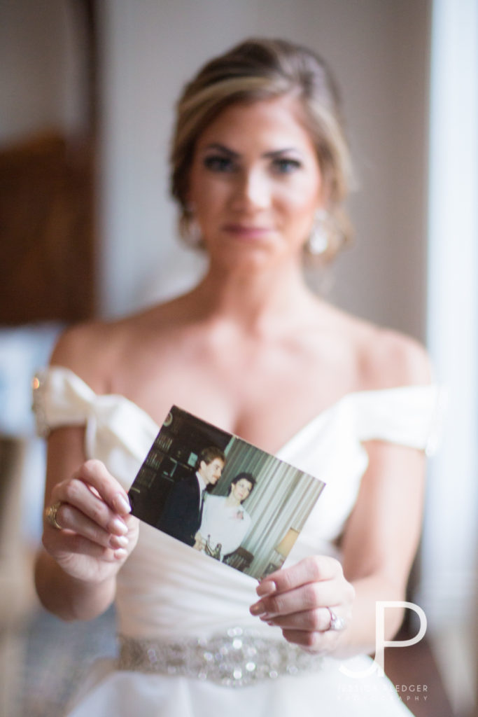 Bride holding parent's wedding photo